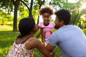 Playful African American family having fun in the park