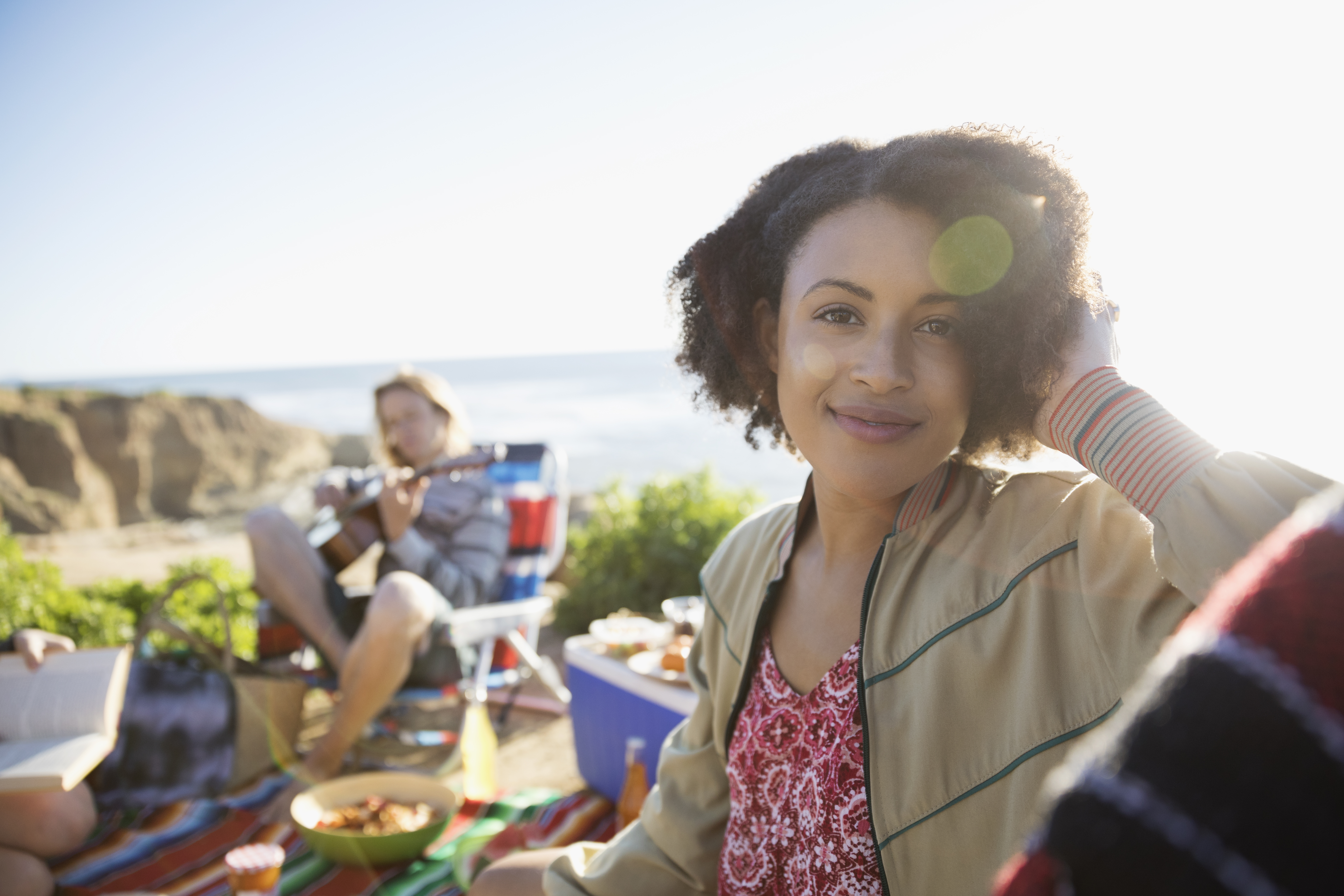 Portrait smiling young woman enjoying picnic with friends on sunny beach