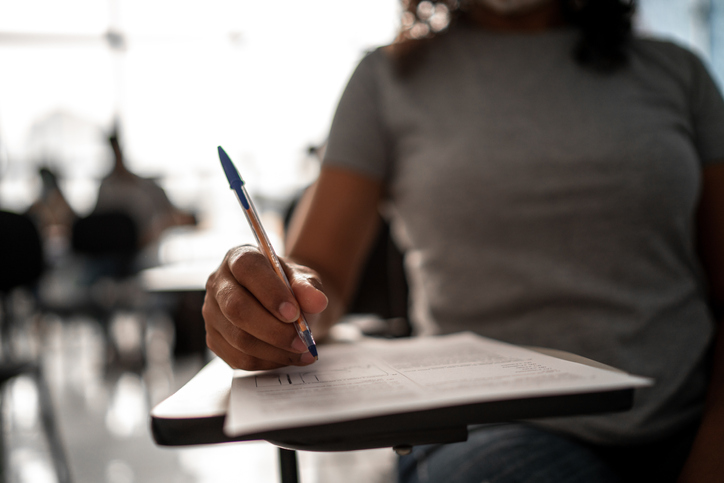 Female hands of a student taking a test
